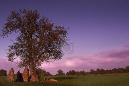 Photo pour Femme Cape noire, visite d'un groupe de trois menhirs et un arbre solitaire - image libre de droit