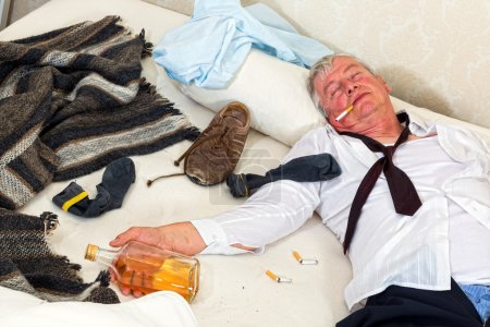 Photo for Drunken alcoholic sleeping in a messy bed - Royalty Free Image