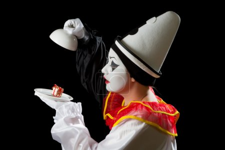Mime Pierrot actor finding a gift under on a white...