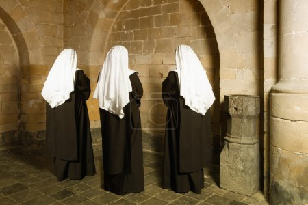 Photo for Young nuns facing the walls of a 14th century medieval abbey - Royalty Free Image
