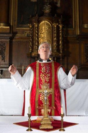 Photo pour Prêtre catholique récitant une prière lors de la messe dans une église médiévale à l'intérieur du XVIIe siècle (y compris la peinture ) - image libre de droit