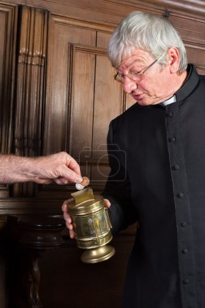 Photo for Priest collecting money in church for fundraising - Royalty Free Image