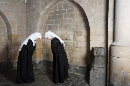 Photo for Two nuns greeting eachother inside a medieval abbey - Royalty Free Image