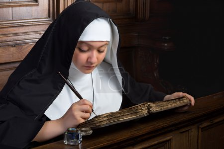 Photo for Vintage scene of a young nun writing in an ancient book - Royalty Free Image