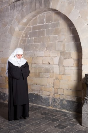 Photo for Young novice standing near the old walls of a medieval church - Royalty Free Image