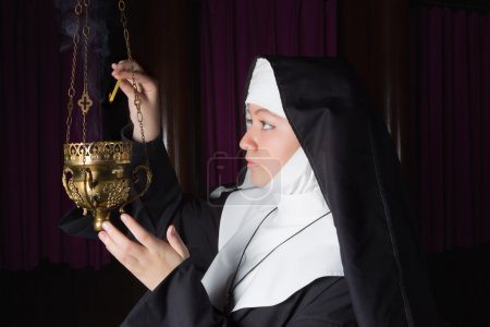 Nun burning incense