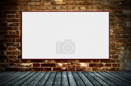 Photo for Illuminated blank advertising billboard on a brick wall - Royalty Free Image