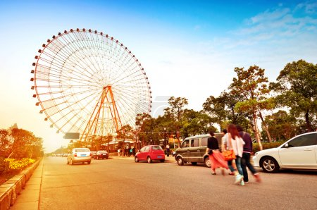 Photo for Evening, ferris wheel, following the crowd. - Royalty Free Image