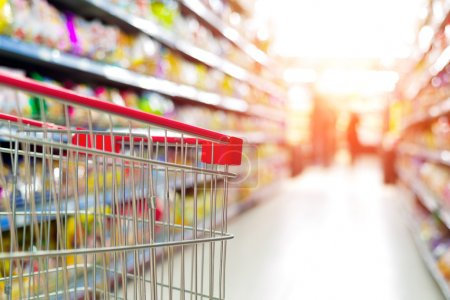 Photo for Supermarket interior, empty red shopping cart. - Royalty Free Image