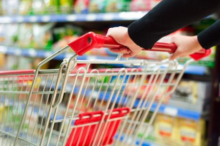 Photo for Lady pushing a shopping cart in the supermarket. - Royalty Free Image