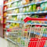 Supermarket interior, empty red shopping cart....