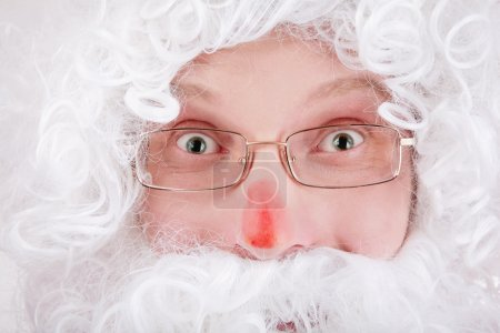 Close-up portrait of guy in white wig and beard of Santa Claus with crazy facial expression
