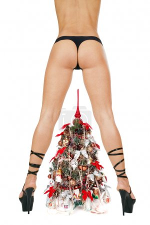 Beautiful woman's bottom and legs in black hyper-sexy stilettos and decorated New Year tree