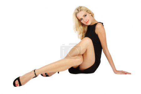 Photo for Beautiful slim blonde girl in cocktail dress sitting on white background with crossed legs - Royalty Free Image