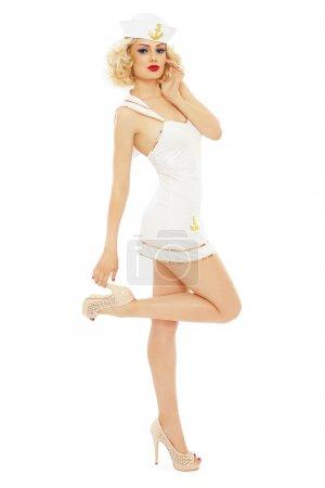 Photo pour Jeune belle fille sexy mince avec des cheveux bouclés blonds et un maquillage élégant habillé en marin, sur fond blanc - image libre de droit