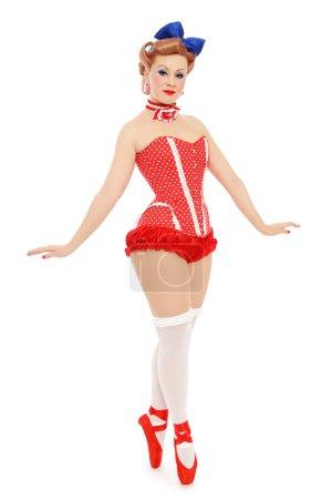 Photo pour Belle jeune fille pin-up sexy en corset à pois et chaussures de ballet rouge sur fond blanc - image libre de droit