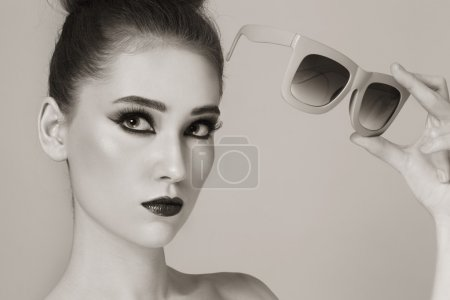 Photo for Duotone portrait of young beautiful stylish girl with vintage sunglasses in her hand - Royalty Free Image