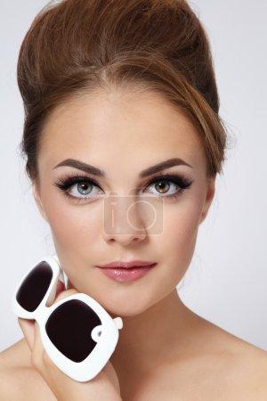 Photo pour Portrait de jeune belle fille élégante avec des lunettes de soleil vintage dans sa main - image libre de droit