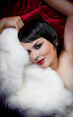 seminude beautiful short haired brunette woman lying on red silk