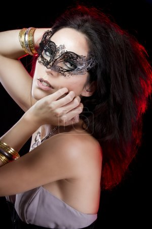 Sexy woman with bracelets of gold and silver, venetian mask with