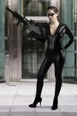 Sexy woman holding gun wearing a black leather dress