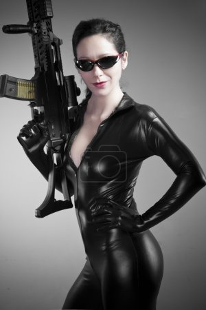 Sexy brunette woman in latex jumpsuit with heavy gun