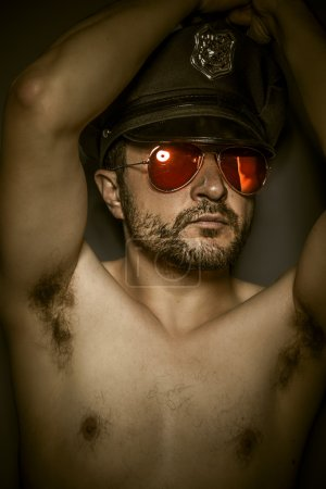 Sexy police, naked man with cap and red mirror glasses