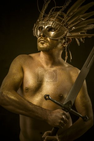 Combative, warrior or ancient god with golden mask and sword gre