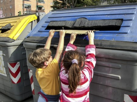 Children pulling a cardboard into recycling container for paper