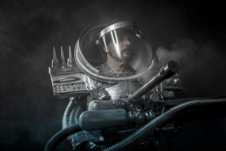 Photo pour Astronaute forte sur un fond noir avec une arme énorme. - image libre de droit