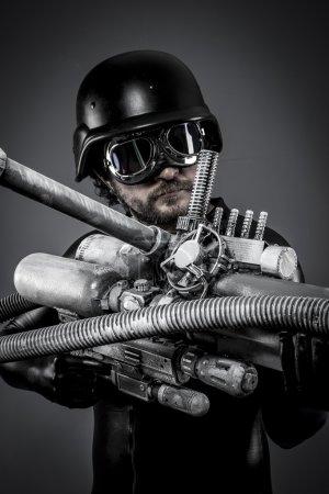 Photo pour Starfighter avec un énorme fusil à plasma, concept fantastique, casque militaire et lunettes motocycliste. airsoft - image libre de droit
