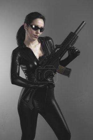 Photo pour Mitrailleuse, femme brune avec des énorme gilet pare-balles et fusil - image libre de droit