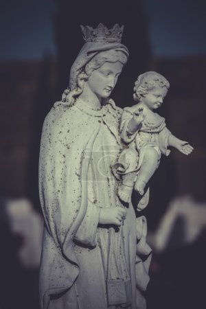 sculpture of the Virgin Mary in a cemetery