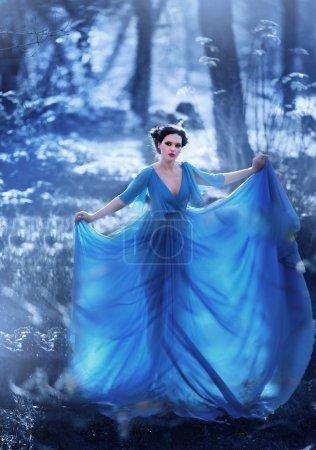 Photo pour Belle fille en robe bleue, marcher dans la forêt magique - image libre de droit
