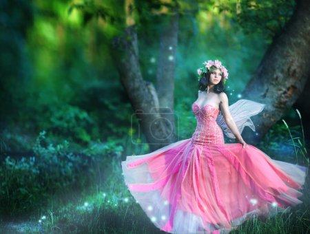 Photo pour Charmante nymphe de femme avec une couronne de fleurs dans la forêt - image libre de droit