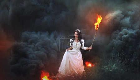 Photo for Beautiful brunette with torch in forest, on black smoke background - Royalty Free Image