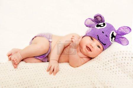 A newborn baby in purple knitted cap
