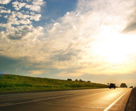 Car on highway, summer sunset