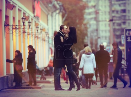 Lovers kissing and cuddling on a city street with passers