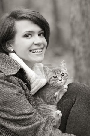 Girl and a cat in the autumn park