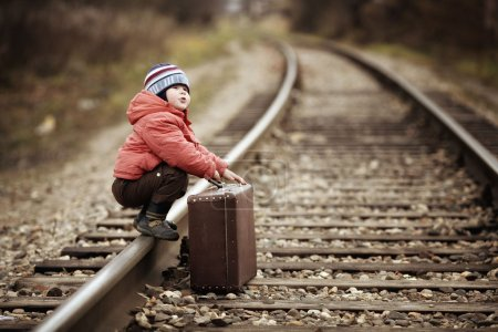 Photo for Boy sitting in a suitcase near the railway journey - Royalty Free Image