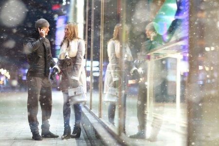 Photo pour Homme et femme amoureuse près de vitrine à l'extérieur dans la neige de l'hiver. homme au téléphone - image libre de droit