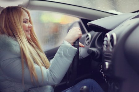 Photo for Pretty Blonde woman in car. Hands on wheel - Royalty Free Image