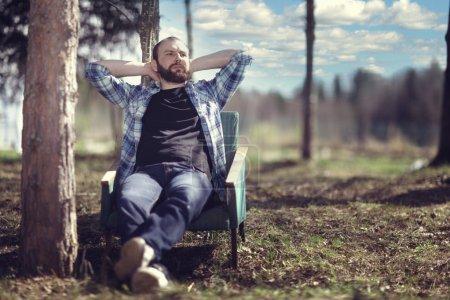 Photo pour Homme barbu assis dans une chaise et se reposant dans le bois d'automne - image libre de droit