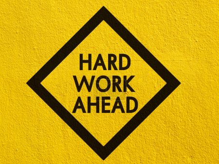 Hard work ahead street sign painted on a stucco wall outside
