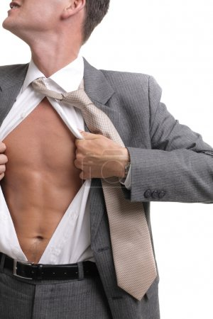 Release! - young businessman dressed in suit, shirt and tie pulling his shirt open revealing well-built torso