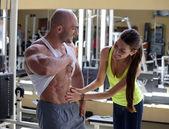 Woman checks abdominal muscles athlete