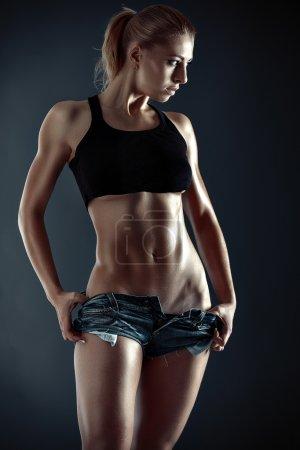 Photo pour Jeune fille avec une figure du sport sur un fond sombre - image libre de droit