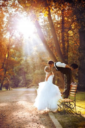 European bride and groom kissing in the park
