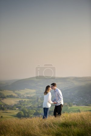 Young couple kissing on a hill